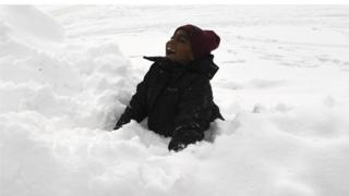 A boy smiles and plays in the snow