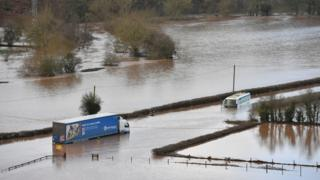 A lorry and a coach submerged in floodwater from the River Teme on the A443 near Lindridge, Worcestershire