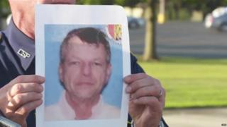 A police officer holds an image of John Houser at a news conference in Lafayette. Louisiana - 24 July 2015