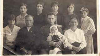 Слева направо, первый ряд: дочь Анна, Яков Митрофанович, сын Константин (отец Якова) на руках внучка Я.М. и А.Г. Светлана, Анна Гавриловна; второй ряд: дочери Ульяна, Екатерина, Мария, Татьяна, Зоя. Мурманск, 1938 год
