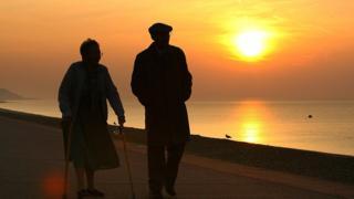 Yaşlı çift güneş batımında yürüyor