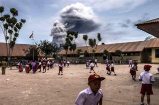 Student play outside their classrooms while Mount Sinabung spews volcanic ash