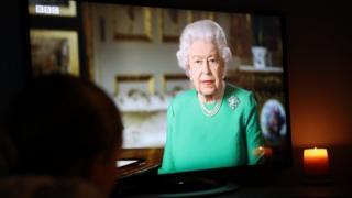 A young girl watches Queen Elizabeth II deliver her address to the nation and the Commonwealth