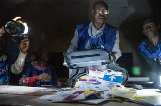 Independent National Electoral Commission (CENI) agents count votes during an electricity cut while watched by observers at Kiwele college in Lubumbashi on 30 December 2018, following the close of polls in the country's presidential, provincial and national elections.
