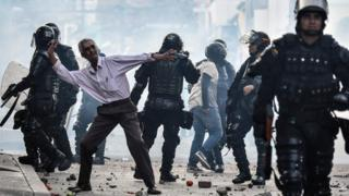 A demonstrator throws stones during a protest against a campaign rally by Timochenko in Yumbo, Colombia, on February 7, 2018