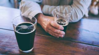 Мушкарац пије црно пиво