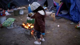 in_pictures A Mexican girl tries to warm herself by a fire as temperatures dropped in Ciudad Juarez