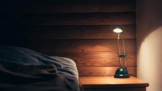 Lâmpada acesa ao lado da cama