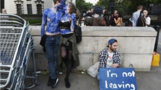 A young couple painted as EU flags, protest outside Downing Street against the UK's decision to leave the EU