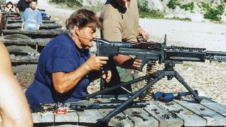 Женщина стреляет из пулемета