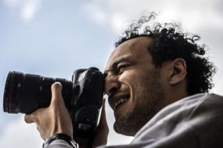 Egyptian photojournalist Mahmoud Abu Zeid, widely known as Shawkan, carries a camera at his home in the capital, Cairo, on 4 March 2019.