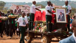 Pallbearers guard the coffin of Jonas Savimbi, a former leader of the UNITA movement, as it is carried during the reburial of the remains on June 1, 2019, in his home village of Lopitanga, near the town of Andulo, in Bie Province in Angola