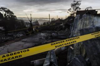 Houses destroyed by bushfire are seen at dawn on March 25, 2018 in Tathra, Australia.