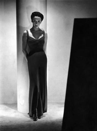 Eve Curie, Madame Curie's daughter, wearing long, form-fitting dress of softly draping dark fabric, by Schiaparelli.