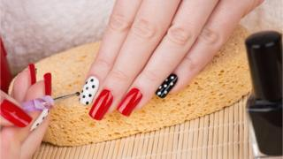 Applying nail art to hands with red, white and black nail polish