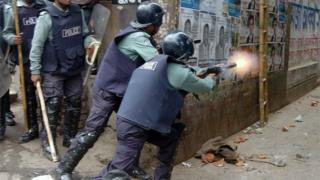 File photo of a Bangladeshi policeman firing tear gas at opposition activists