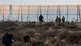Migrants run after crossing the Mexico-US border fence in Tijuana, Mexico