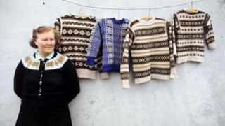 A woman poses wearing a Fair Isle style cardigan in front of Fair Isle jumpers hanging on a line in front of the wall of a cottage on one of the Shetland Islands in 1970.