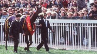 Red Rum being led past spectators