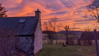 A sunset over a house and fields