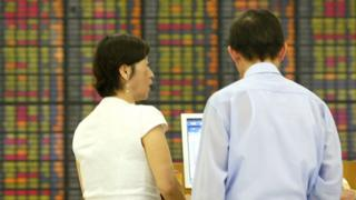 People look at stock market boards in Asia