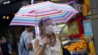 A woman shields from rain on Oxford Street in London