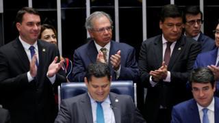 O senador Flávio Bolsonaro e o ministro Paulo Guedes (na foto, à esquerda e em pé) e o presidente da Casa, Davi Alcolumbre (sentado, ao centro), entre outros, comemoram aprovação de texto-base no Senado