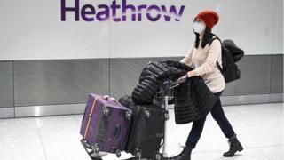 A woman pushing luggage through Heathrow airport