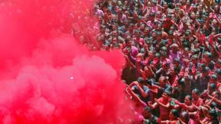 A group of people are sprayed with colours during celebrations in Ahmedabad