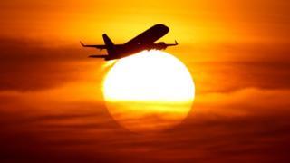Avión vuela sobre el sol.