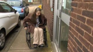 Ali Wilkin in a wheelchair outside the benefits office in Colchester.