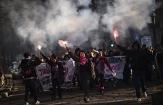 Women light flares during a protest rally in Milan, Italy