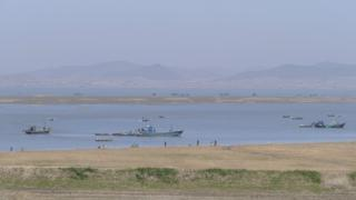 Fishing fleet and offshore mudbank in the estuary of the Chong Chon River, North Korea