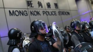 Hong Kong riot police stand guard as anti-government protesters gather outside the Mong Kok Police station
