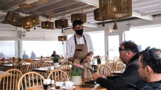 A waiter serves patrons in Mykonos