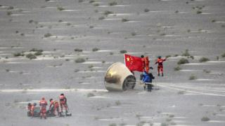 People with a Chinese flag retrieving a module from the desert, 26 June 2016
