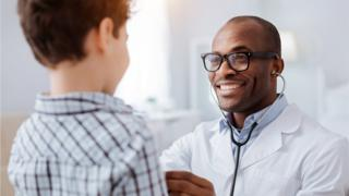 Doctor checks a boy's heartbeat