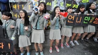 Secondary school students cheering on classmates during exam season in South Korea