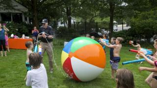 A ring of children spray vice president Joe Biden with a water gun, which he returns in kind. A giant, chest-high beach ball lies between them.