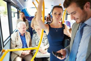 A man looks at his mobile phone on a bus. A woman looks disapproving, (posed by models)