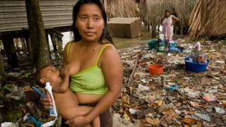 Warrau woman nursing child in a trash laden village on the shores of the Orinoco River in Venezuela.