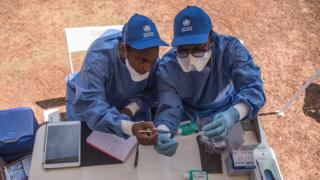 Nurses working with the World Health Organization (WHO) prepare to administer vaccines