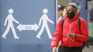 Woman in mask walks past social distancing instructions in Leeds
