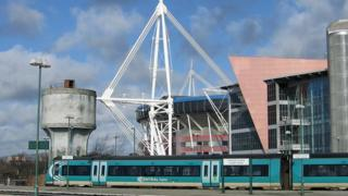 A train at Cardiff station with the Principality Stadium in the background