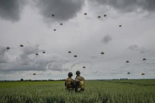 Military re-enactors look on as 280 paratroopers take part in a parachute drop onto fields at Sannerville on 5 June 2019 at Sannerville, France.
