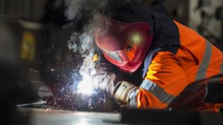 Steel worker cutting metal