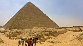 A horseman waits with his horses for tourists in front of Egypt's Cheops Pyramid at Giza plateau south of Cairo 13 June 2002.