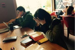 Cafe in China with a woman holding her head in her hands in front of a Bible, and a man on his mobile phone in front of his laptop.