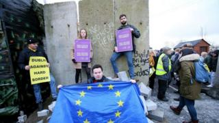 An EU activist holds an EU flag at a mock wall erected during a protest by an anti-Brexit campaign group on a road crossing between Northern Ireland and Ireland in Newry, Northern Ireland, on January 26, 2019