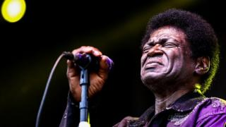 Charles Bradley seen in close-up, eyes closed in front of a stage microphone, wearing a sequined purple coat